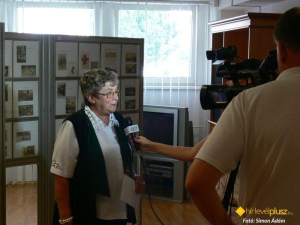 Kőszegfalviné Pajor Klára interjút ad a Szombathelyi Televíziónak a képeslevelezőlap-gyűjtők kiállításán, 2013 júliusában