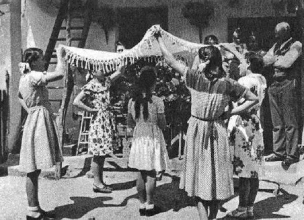 A felkeresett ház udvarán a pünkösdölők körülállják a királynét (Nemesládony, Vas m., 1952) (Forrás: Magyar Néprajzi Lexikon, mek.oszk.hu)